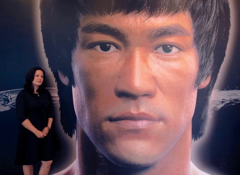 Shannon Lee, daughter the late Kung Fu legend Bruce Lee, poses beside a portrait of her father at the Hong Kong Heritage Museum