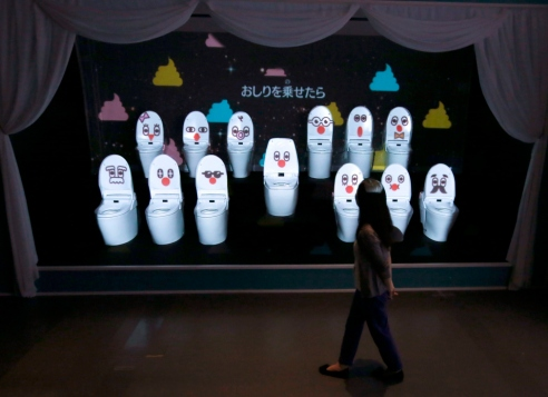 "Woman walks past a choir of toilets at an exhibition titled ""Toilet !? Human Waste and Earth's Future"" at Miraikan National Museum of Emerging Science and Innovation in Tokyo"